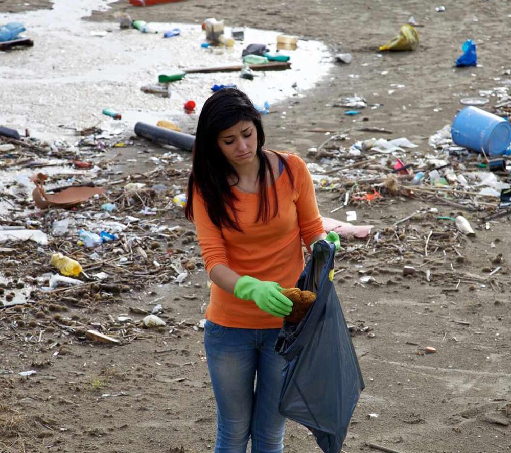 从海滩收集塑料的女孩